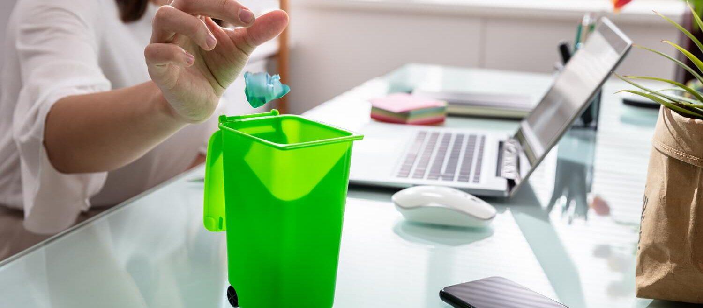Kobieta wrzucająca śmieci do małego biurowego kosza